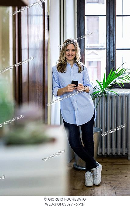 Portrait of smiling woman with cell phone at home