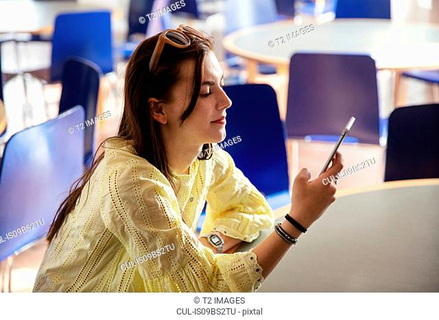 Teenage girl reading text message on cellphone in school