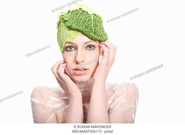 Portrait of young woman with cabbage cap against white background, close up