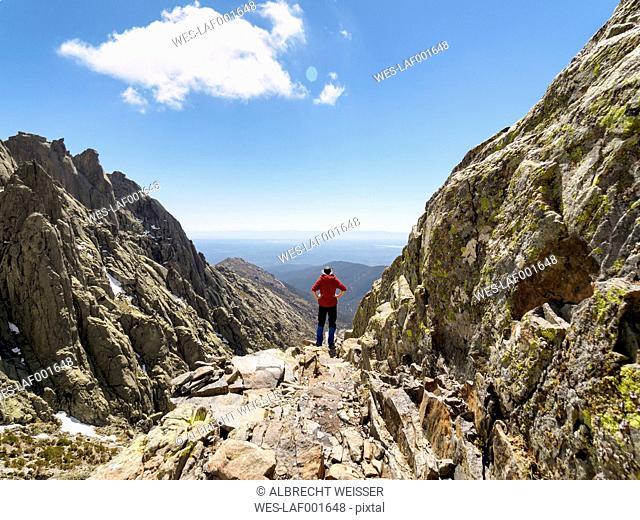 Spain, Sierra de Gredos, hiker standing on rock in mountainscape