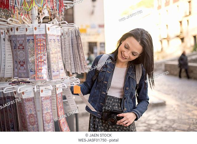 Spain, Granada, smiling young woman at Albayzin district at a souvenir stall
