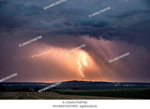 Cloud-to-ground lightning illuminated precipitation on the backside of a leaving supercell near Feuchtwangen, Baden-Wuerttemberg, Germany