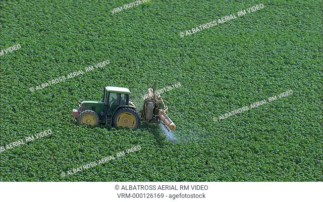 Aerial HD shot of a tractor spraying a plowed field