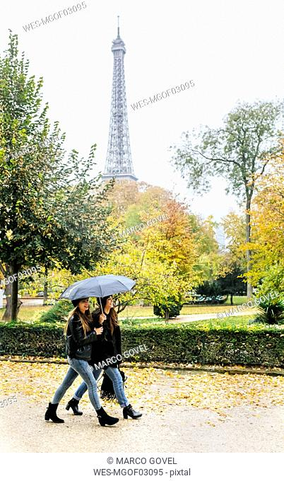 France, Paris, two young women walking in park with the Eiffel Tower in the background