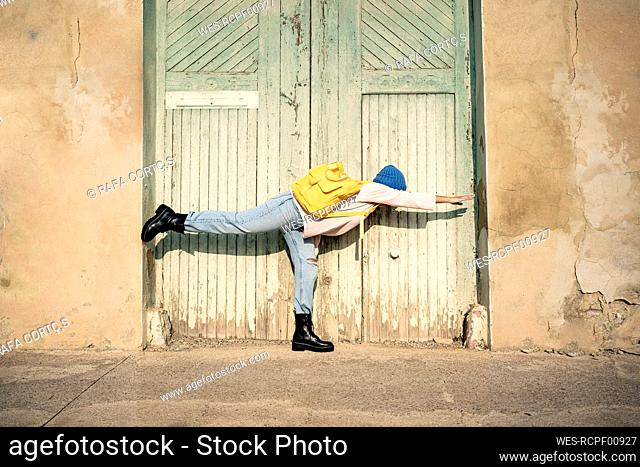 Woman with backpack stretching hand while standing on one leg during sunny day