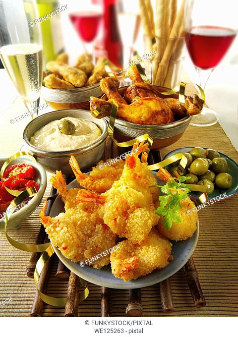 Party food with breaded butterfly prawns, chicken drum sticks and tappas