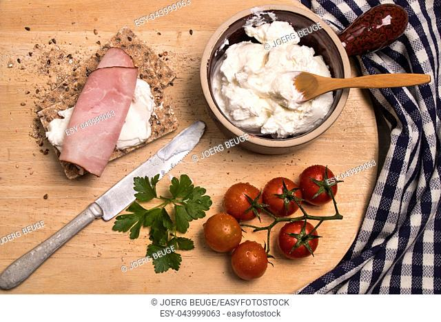 healthy breakfast with crispbread, quark, parsley and smoked ham on a wooden board