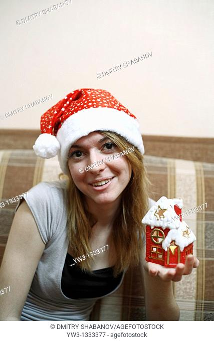 pretty girl in the Christmas hat on sofa with little red xmas house in hands