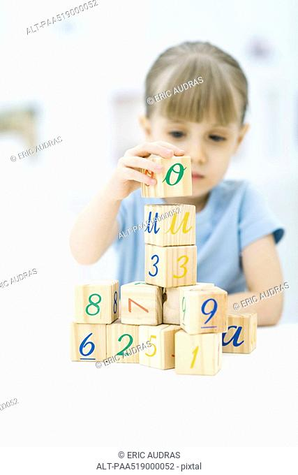 Little girl stacking blocks, focus on foreground