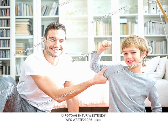 Boy flexing muscles for father at home
