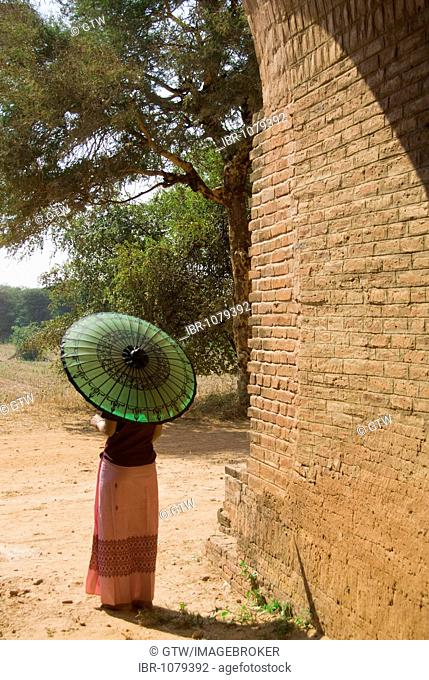 Back view of a young Burmese woman with a green parasol, Bagan, Myanmar