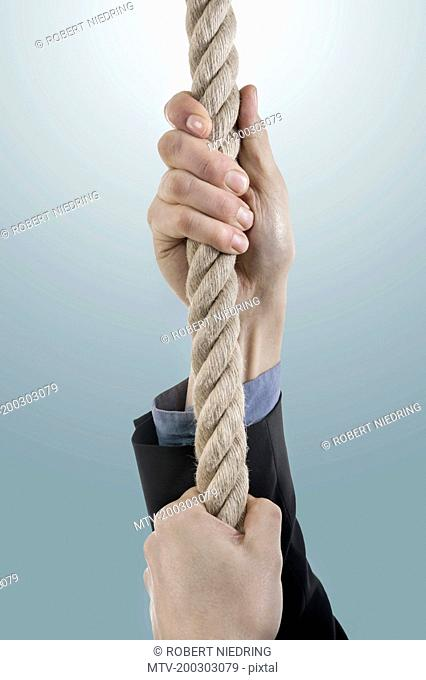 Businessman's hands pulling rope, Bavaria, Germany