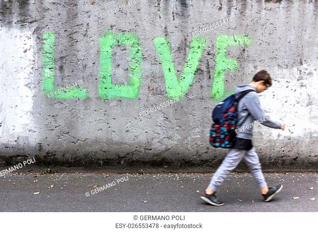 """A schoolboy walking down the street with head bowed; on the wall stands the inscription """"""""LOVE"""""""""""