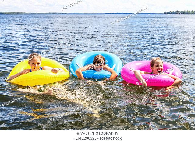 Three kids playing in Balsam Lake wearing colorful inflatable rings; Ontario, Canada