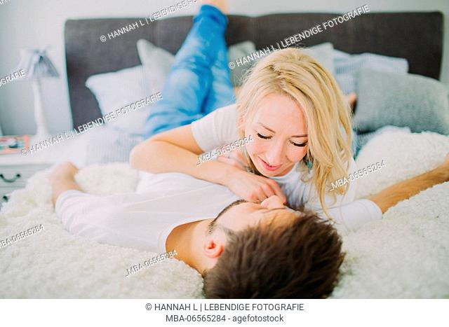 Young couple in love at home in the bed