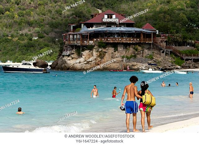 Young couple stroll beach at Baie de St Jean Eden Rock Hotel in distance St Barts
