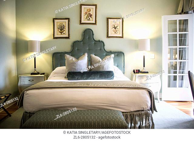 Beautiful old fashion soft green headboard bed with double french doors that opens to a Suite in an bedroom of an Inn