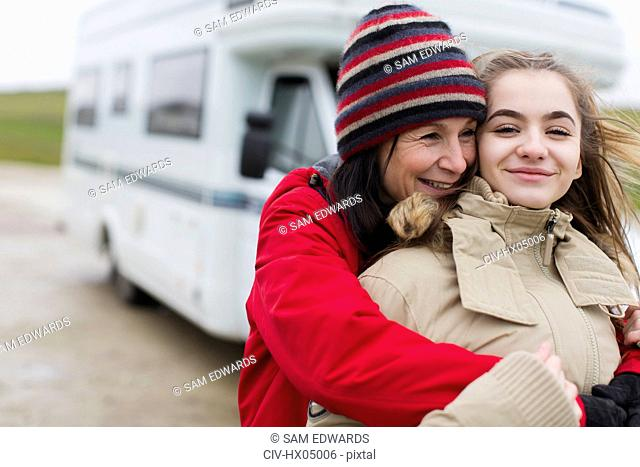 Affectionate mother and daughter in warm clothing hugging outside motor home