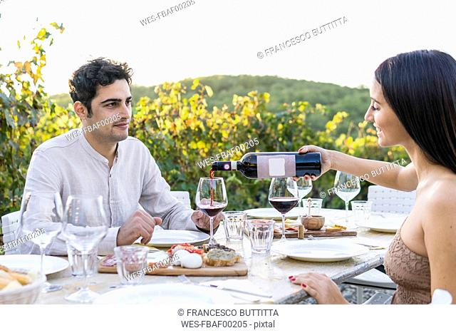 Italy, Tuscany, Siena, young couple having dinner in a vineyard with red wine