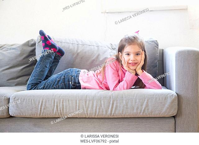 Portrait of smiling little girl lying on the couch