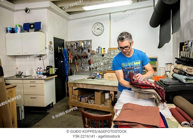 Tilburg, Netherlands. Josef is an apprentice upholsterer, replacing a pile of cloth in his workshop., before taking on a new project