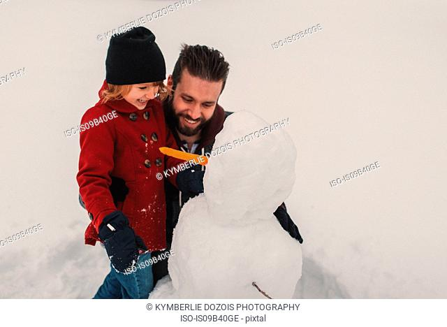 Father and daughter making snowman