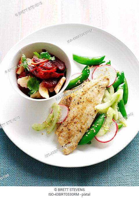 Plate of fish with beans and fruit salad