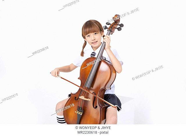 Elementary school girl in school uniform sitting and playing the cello