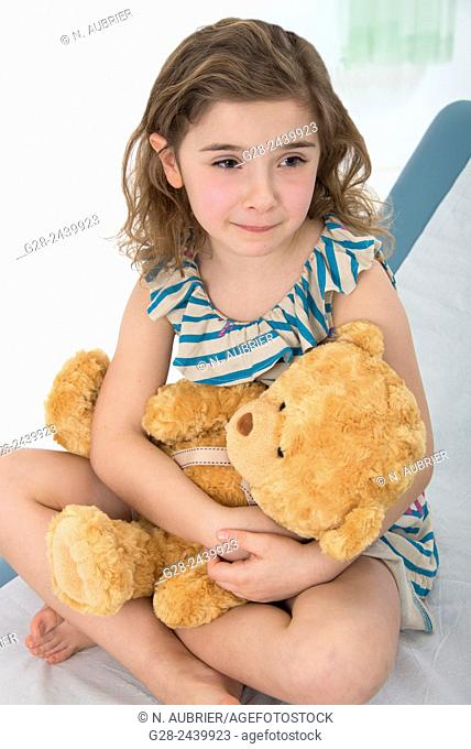 Worried and crying little girl sitting on a medical couch holding her teddy bear