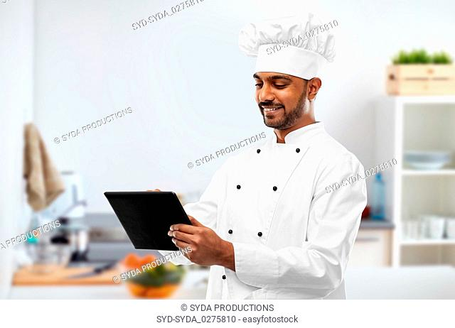 happy indian chef with tablet computer at kitchen
