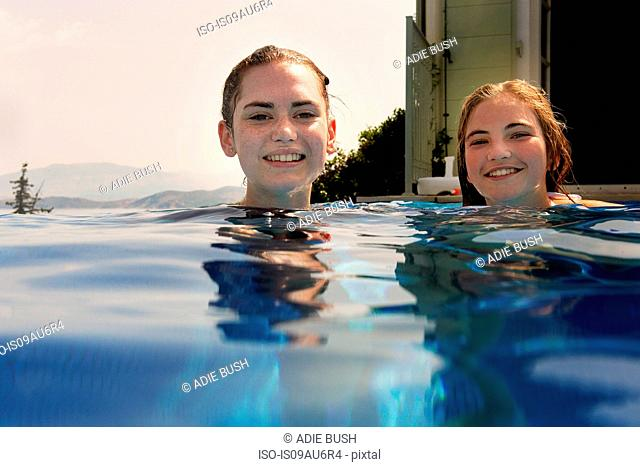Surface level portrait of teenage girls in outdoor swimming pool