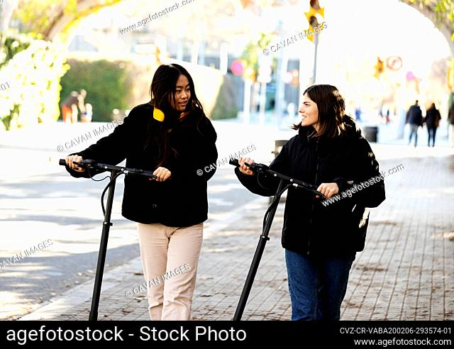 Two young women riding e scooters in Barcelona sidewalk