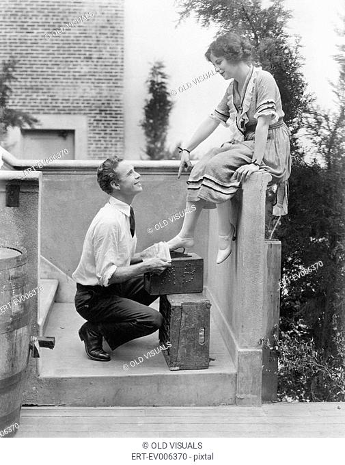 Woman sitting on a ledge having her shoes cleaned by a man All persons depicted are not longer living and no estate exists Supplier warranties that there will...