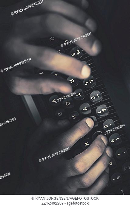 Dark creative writing concept of hands typing the keys to a fictional novel on an old typewriter. The mystery writer