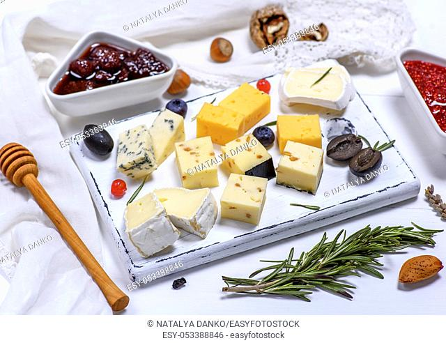 small pieces of brie cheese, roquefort, camembert, cheddar and cheese with walnuts on a white wooden board, top view