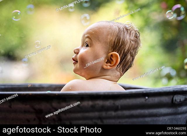 Baby boy having fun in a metal bath tub with bubbles