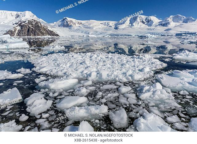 Ice choked waters surrounded by ice-capped mountains and glaciers in Neko Harbor, Antarctica