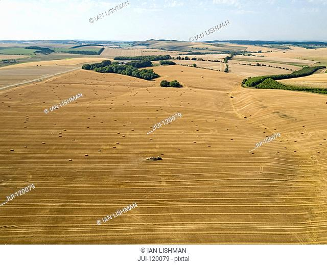 Aerial landscape of tractor baler straw bales in farm fields after wheat harvest in summer