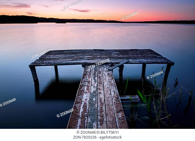 Small wooden pier on big lake at sunset