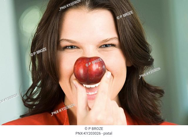 Woman holding a nectarine in front of her nose