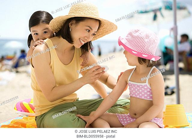 Asian mother applying sunscreen to daughter