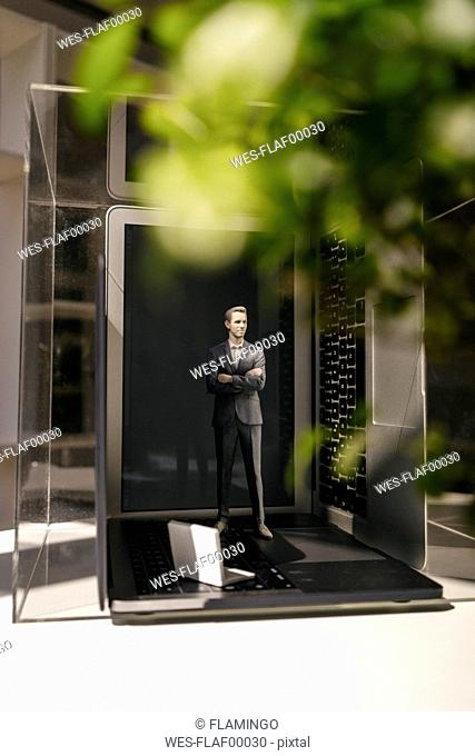 Businessman figurine standing on portable devices under a green plant