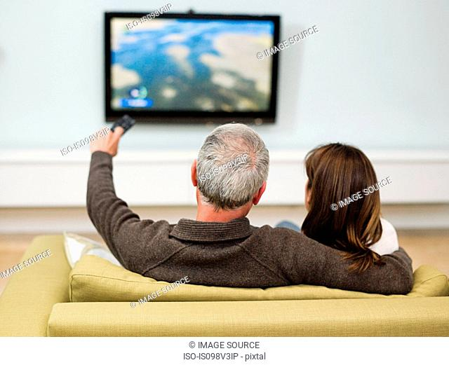 Mature couple sitting on sofa watching television