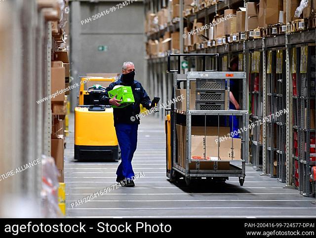 16 April 2020, Brandenburg, Großbeeren: A worker wearing a face mask checks the goods at the logistics service provider Rhenus Warehousing Solutions SE & Co