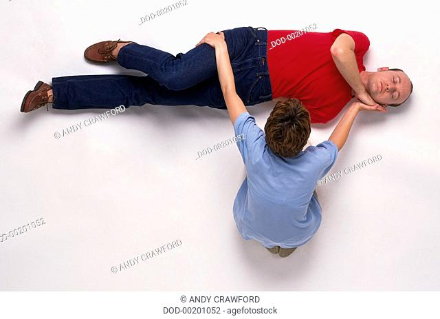 Carer positioning one arm under casualty's head and pulling leg towards her