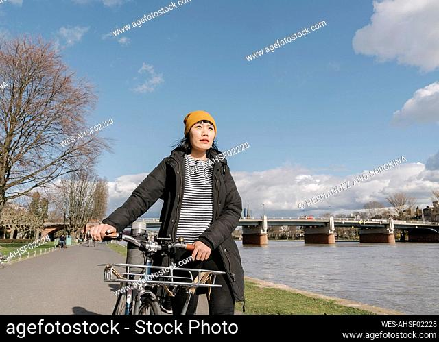 Woman with bicycle on the riverbank, Frankfurt, Germany