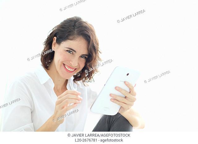 Woman using tablet computer and smiling at camera