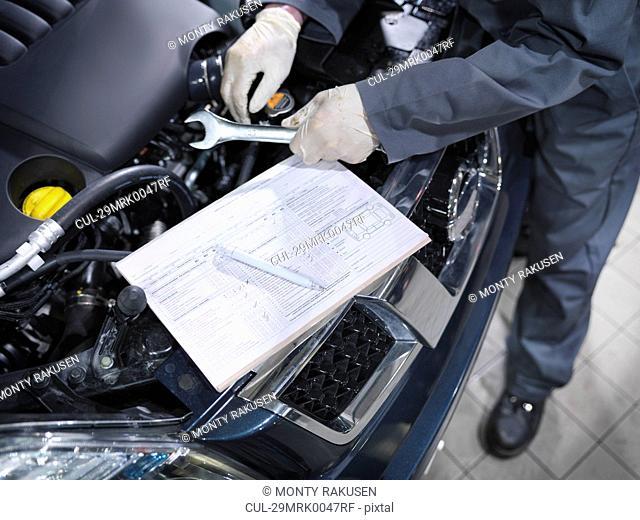 Mechanic checks list in car dealership