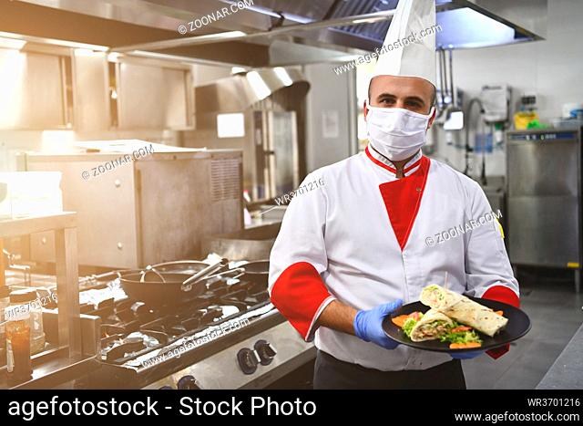 chef cook wearing face protective medical mask for protection from corona virus disease with plate of authentic sandwich at professional restaurant kitchen