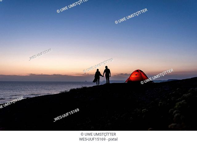 Romantic couple camping on the beach, walking in twilight, holding hands